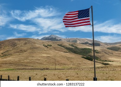 American national flag flies over the rural landscape of Texas. The barren hills rise in the distance and the top of a wooden fence sits in the foreground. Flag flies to the left in a brisk breeze,