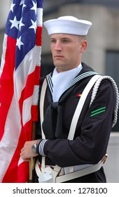 An American navy holding US.  flag