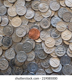 American one cent coin on pile of 10 cent coins
