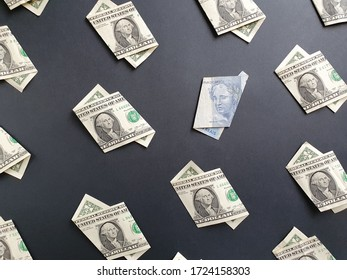american one dollar bills and brazilian banknote of two reais on the black background