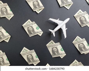 american one dollar bills and figure of a white plastic airplane on the black background