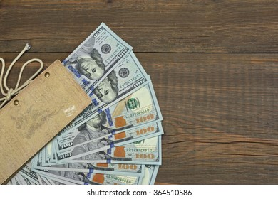 American One Hundred Dollar Bills In The  Notepad Top View On The Rough Wooden Table Background With Copy Space