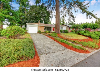American one story rambler house exterior. Tile roof, red brick wall and gray clapboard siding. Northwest, USA