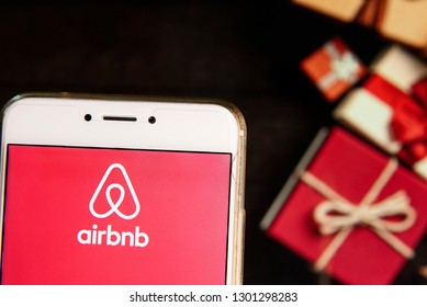 American online marketplace and hospitality service Airbnb logo is seen on an Android mobile device with a Christmas wrapped gifts in the background.