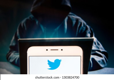 American online news and social networking service Twitter logo is seen on an Android mobile device with a figure of hacker in the background.
