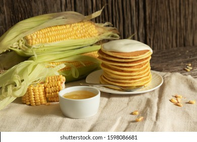 American pancake with cornmeal cream on a rustic wooden background. Minimal style in natural colors. Diet menu and vegetarian dish. Ears of corn and slices next to bowls. Gluten-free healthy foods. Ho