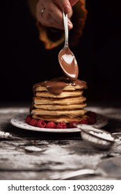 American pancakes isolated on plate with woman hand adding chocolate cream with spoon.