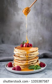 American pancakes with raspberries, mint and honey on grey concrete background. Stack of pancakes.