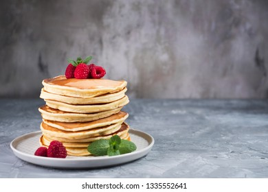 American pancakes with raspberries and mint on grey concrete background. Stack of pancakes.