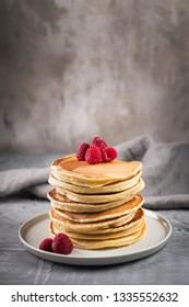 American pancakes with raspberries on grey concrete background. Stack of pancakes.
