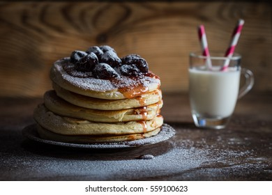 American pancakes served with cherry jam and powdered sugar on a wooden background