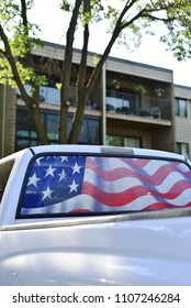 American patriot with rear window of truck replaced with the United States national flag.