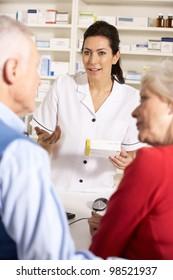 American pharmacist dispensing to senior couple