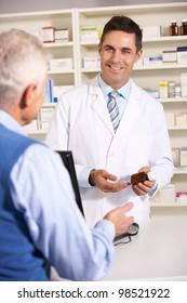 American pharmacist with senior man in pharmacy