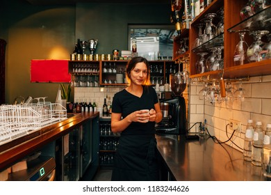 American plan portrait of a young girl bartender holding a cup of coffee on her hands and wearing a black apron