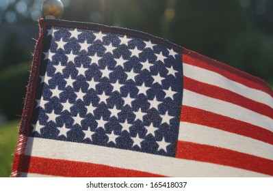 American Pride Concept.  A close-up backlit American flag outdoors.