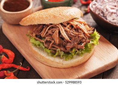American pulled pork burger sandwich with lettuce and various dips