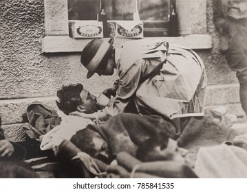 American Red Cross nurse aiding wounded soldiers at Montmirail, France, May 31, 1918. She helps a soldier drink from a cup as he lies on a railroad platform awaiting evacuation