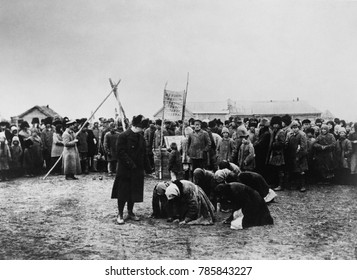 American Relief Administration distributing food in the Volga District, 1921. Russian women abjectly kneel nearby
