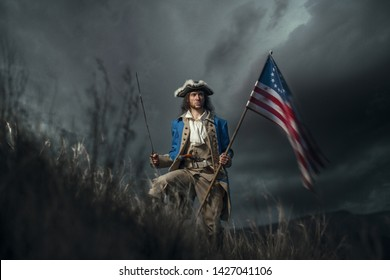 American revolution war soldier with flag of colonies and saber over dramatic landscape. 4 july independence day of USA concept photo composition: soldier and flag.