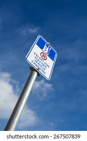 An American road sign. EV - electric vehicle charging station, with parking exception warning below. Electric car charging point road sign on blue sky background.