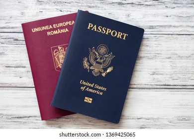 American and romanian passports flat lay on a wooden background. Double citizenship concept.