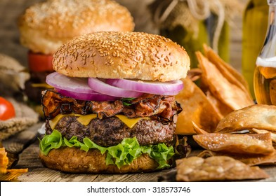 American rustic bacon burger with cheddar, beef, salad and vegetable, old school picture, with czech beer and original homemade nachos with honey mustard dip, place for advertising