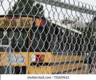American School Bus Parked Behind Chain Link Fence