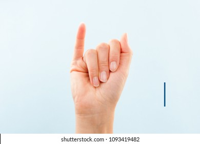 American sign language. Female hand showing letter I isolated on blue background.