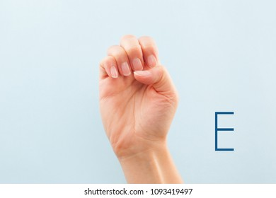 American sign language. Female hand showing letter E isolated on blue background.