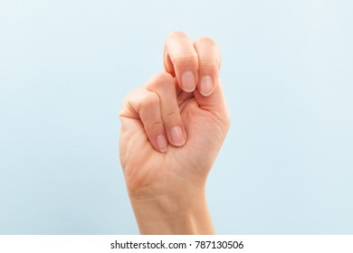 American sign language. Female hand showing letter N isolated on blue background.