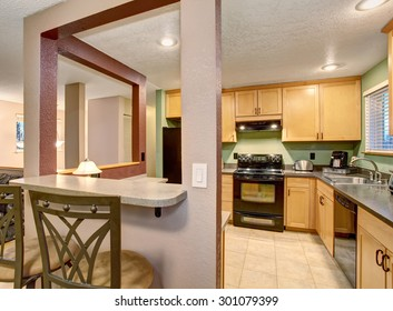 American small house or apartment type typical kitchen for 2014. Tile floor, birch tree light wood cabinets, black color appliances