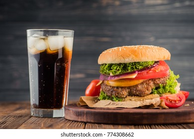 american snack with big burger and glass cola on wooden table