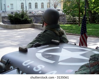 American soldier, armored vehicle and a flag