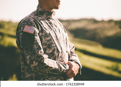 An American soldier looks into the distance at sunset. USA flag on a soldiers hand. United States Army. Veterans Day - Shutterstock ID 1761328949