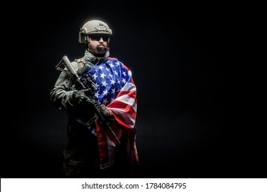 American soldier in military uniform with a gun holds the USA flag against a dark background, the elite troops of America, American special forces
