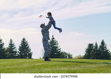 American soldier is playing with his daughter outdoor. Military father is raising up his daughter up, reunion of happy family in the summer park.