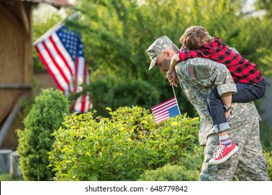 American soldier reunited with son on a sunny day with american flag on the background. Father piggyback his teen son outside