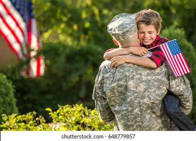 American soldier reunited with son on a sunny day with american flag on the background