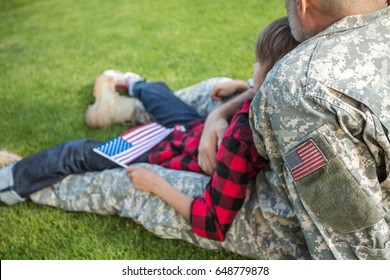 American soldier reunited with son on a sunny day, detail, focus on shoulder with american flag label