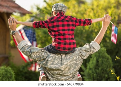 American soldier reunited with son on a sunny day with american flag on the background. father carrying him on shoulders