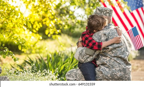 American soldier reunited with son on a sunny day with american flag on the background. wide screen image