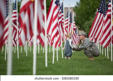 American soldier talking and playing with his toddler daughter among a lot of American flags