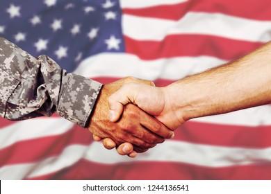 American soldier in uniform and civil man handshake