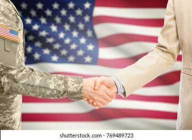 American soldier in uniform and civil man in suit shaking hands with adequate national flag on background - United States of America
