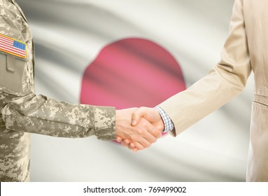 American soldier in uniform and civil man in suit shaking hands with adequate national flag on background - Japan