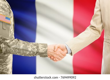 American soldier in uniform and civil man in suit shaking hands with adequate national flag on background - France