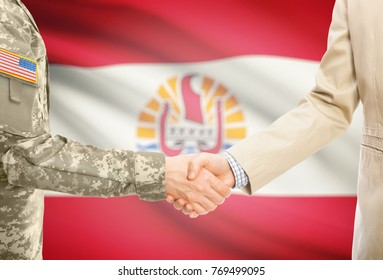 American soldier in uniform and civil man in suit shaking hands with adequate national flag on background - French Polynesia