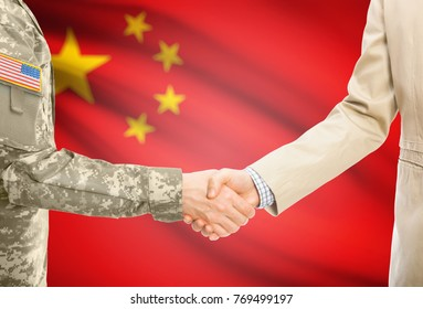 American soldier in uniform and civil man in suit shaking hands with adequate national flag on background - People's Republic of China