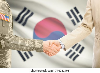 American soldier in uniform and civil man in suit shaking hands with adequate national flag on background - South Korea
